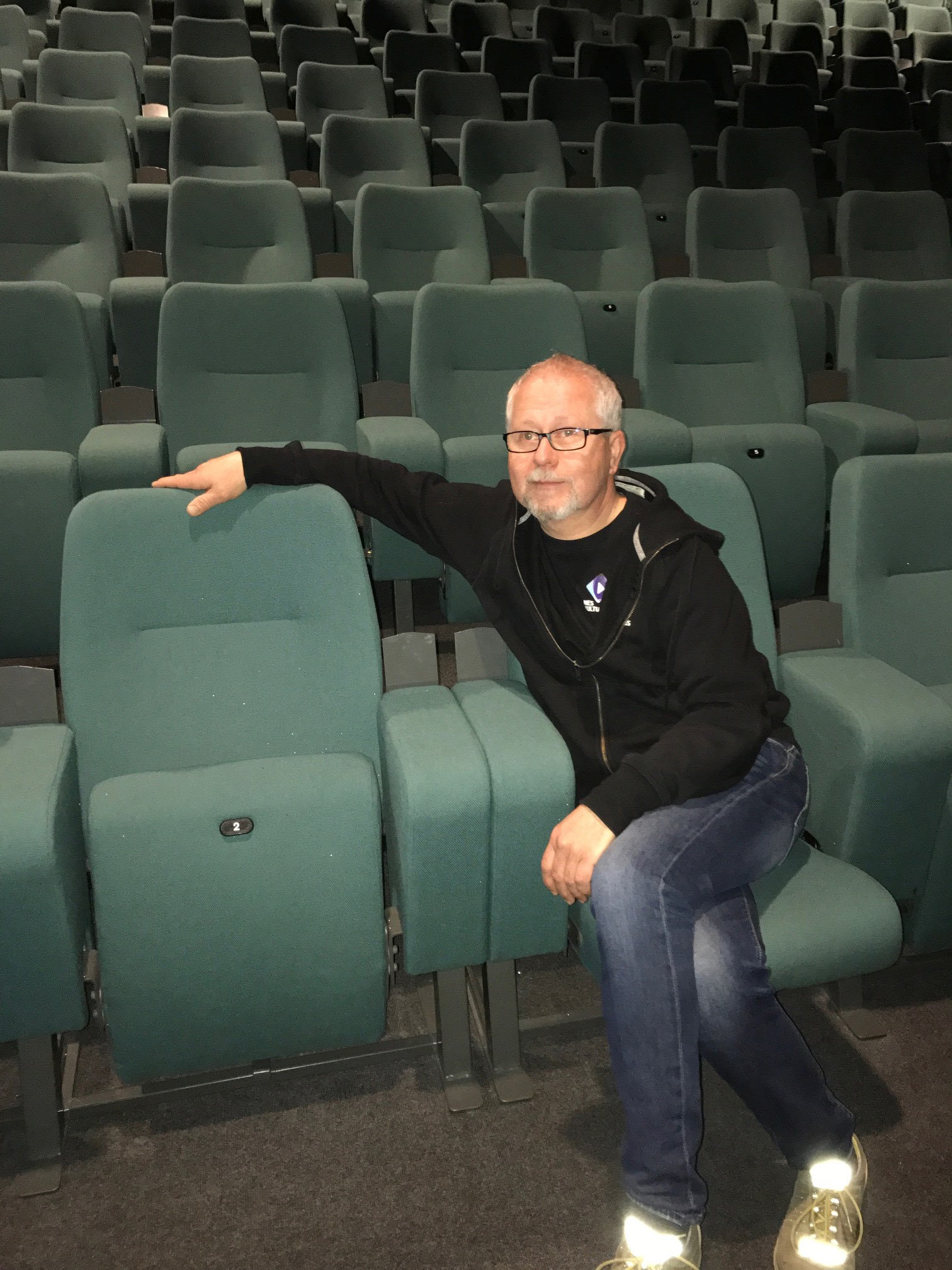 FORBEDRER SEG: Kulturhusleder Jan Magne Hanstad ved Nes kulturhus og Årnes kino inne i salen hvor alle stolene ble trukket om for tre år siden. Stolene er fra Auditoria Services. Foto: Nes kulturhus.
